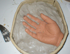 You'll need to build up a wall of waterbased clay around the hand to mark it in half.